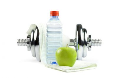 Metal dumbell with green apple, bottle of water and towel. Isolated on white